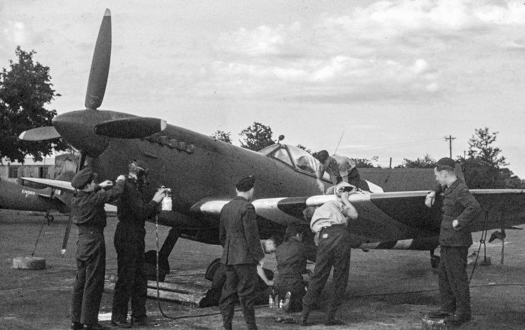 """Medio 1944, RAF Benson: het aanbrengen van """"invasion stripes"""" op een Supermarine Spitfire PR Mark XI. (collectie: Heemkundekring, Budel)"""